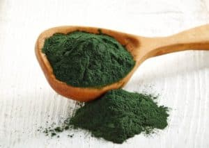 Wooden spoon of spirulina algae powder on wooden background